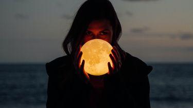vrouw houdt een glazen vol vast die lijkt op de maan