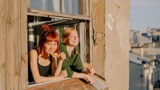 twee vrienden hangen uit raam
