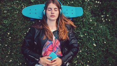 meisje ligt in het gras met skateboard en telefoon