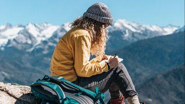 meisje zit op een berg te schrijven