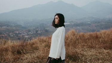 meisje staat alleen voor een berg