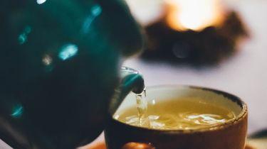 Theepot schenkt thee in een theemok