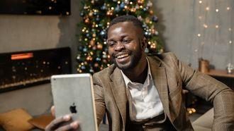 Iemand die kerst viert tijdens corona, door op zijn iPad te videobellen met vrienden