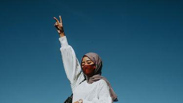 vrouw met hoefdoekje heft haar hand omhoog