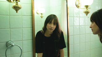 Meisje die in de spiegel kijkt en zoekt naar hormonale acne