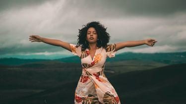 vrouw staat met armen wijd op een bergtop op reis