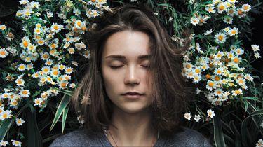 meisje ligt in een bloemenveld