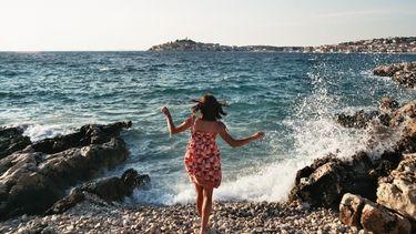 vrouw loopt op rotsen bij zee