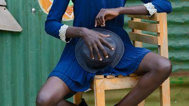 Vrouw op stoel met hoed voor buik