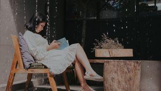 vrouw die alleen een boek leest in een café