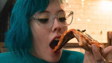vrouw eet pizza