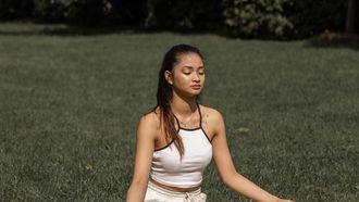 vrouw mediteert in gras