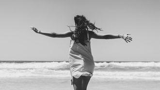 vrouw is blij en loopt over het strand