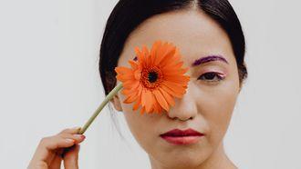 vrouw met bloem voor gezicht