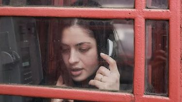 meisje zit aan de telefoon in een telefoonhokje