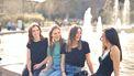 Vier vriendinnen die kletsen bij een fontein