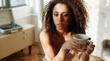 Vrouw met kop koffie in de ochtend