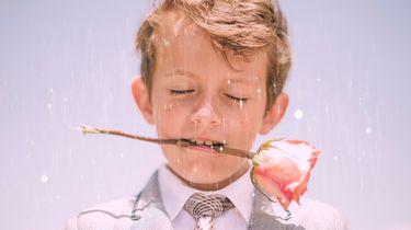 jongen met roos in zijn mond