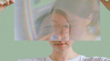 vrouw met een reflectie van zichzelf in een glazen papier