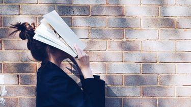 meisje met boek op gezicht