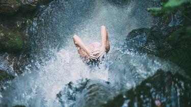 meisje wast zich onder waterval