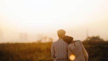 Vrouw zit met hoofd op schouder van haar vriend bij zonsondergang