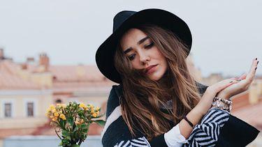 meisje met hoed kijkt serieus