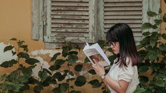 vrouw leest boek in de zon