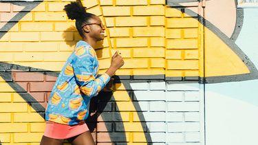 meisje loopt voor gekleurde muur