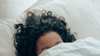 vrouw ligt onder de dekens