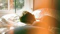 man ligt in bed en is moe