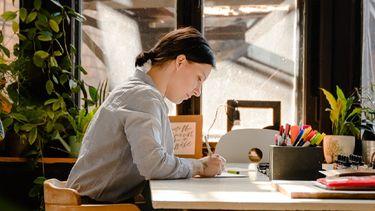 vrouw die aan het lunchen achter haar bureau is
