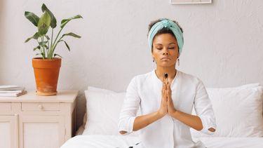vrouw mediteert op bed
