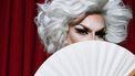 Een drag queen die met een waaier zwaait die ze gekocht heeft in de eerste dragwinkel van Nederland