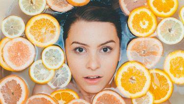 meisje tussen fruitstukken in een bad, natuurlijke badproducten, huidverzorging, droge huid, winterhuid