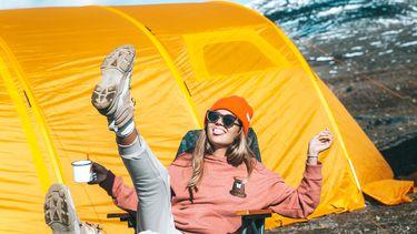 vrouw blij voor kampeertent