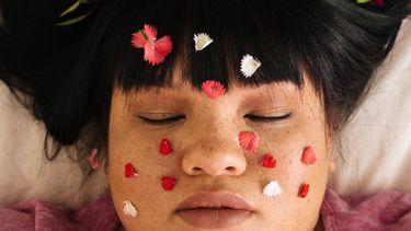 vrouw met rozenblaadjes op gezicht