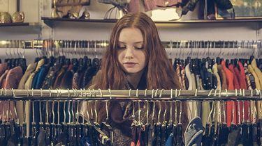 vrouw die kledingstukken bekijkt