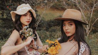 Twee vrouwen liggen in het gras met bloemen