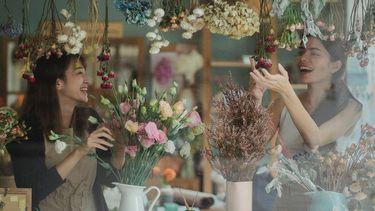 twee vrouwen zijn bezig met bloemen