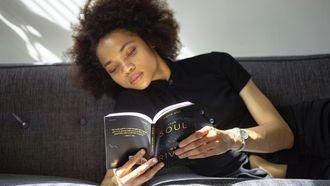 vrouw leest boek op bank