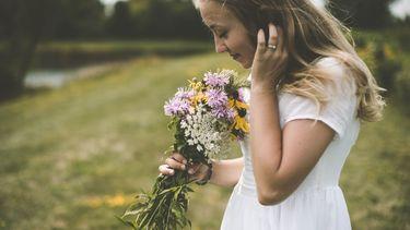 meisje ruikt aan bloemen