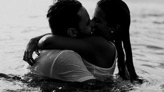 meisje en jongen zoenen in het water