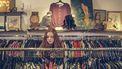 Meisje die tweedehands kleding uitzoekt