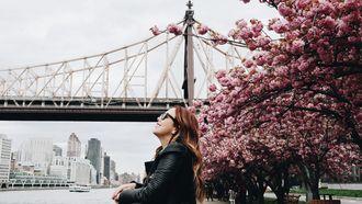 vrouw lacht voor brug en bloemen