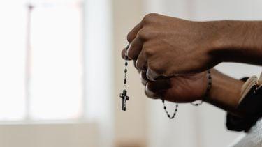 Paar handen die een ketting van een kruis vasthouden