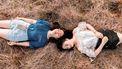 Twee meisjes liggen in het gras