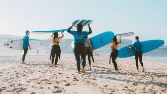 groepsles surfen op strand
