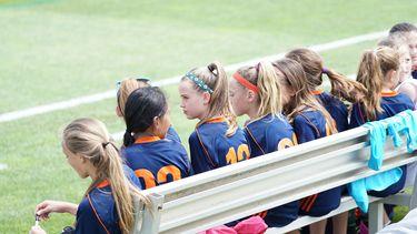 meisjes in sporttenue zitten op een bankje