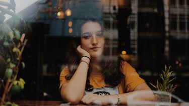 vrouw alleen achter raam